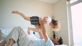 Man raising his son in the air stock footage