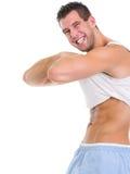 Man raising shirt to show abdominal muscles Stock Photo
