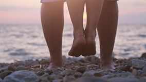 Man raising up on hand her loving woman. Legs of couple in love during the date near the sea on the beach during sunset Stock Image