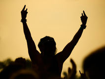 Man raising up hands on rock concert. Silhouette of man raised up hands with rock-n-roll gesture on rock concert with yellow sky in the background Royalty Free Stock Photo