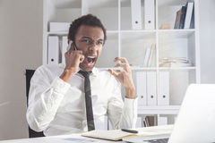Man raising voice on phone. Furious african american businessman sitting at office desk with laptop raising voice at interlocutor over the phone. Concept of Stock Image