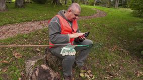 Man with rake sitting and using tablet PC stock footage