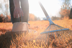 Man with rakes in autumn old grass Stock Images