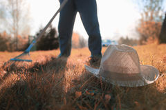 Man with rakes in autumn old grass Royalty Free Stock Photos