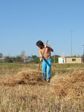 A man rakes the straw. Farmer in field Stock Photo