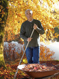 Man raking autumn leaves at edge of lake Royalty Free Stock Images