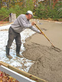 Man raking concrete. To make it level Stock Photo