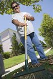 Man Raking Leaves In Lawn Stock Image