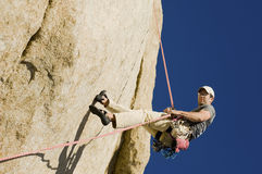 Man Rappelling From Cliff. Low angle view of a young man rappelling from cliff Stock Images