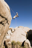 Man Rappelling From Cliff Stock Photo