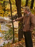 Man at ravine. Man at edge of ravine in autumn pointing at object of interest Stock Image