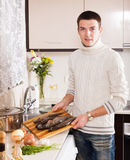 Man with raw trout fish Stock Images