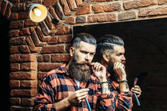 Man with razor near mirror. Handsome bearded man hipster with stylish haircut and beard holding old fashion razor in red checkered shirt near mirror with serious Stock Image