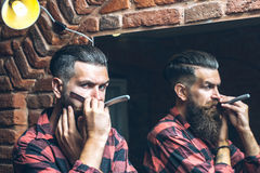 Man with razor near mirror. Handsome bearded man hipster with stylish haircut and beard holding old fashion razor in red checkered shirt near mirror with serious stock photo