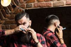 Man with razor near mirror. Handsome bearded man hipster with stylish haircut and beard holding old fashion razor in red checkered shirt near mirror with serious stock photography