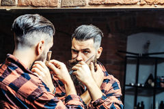 Man with razor near mirror. Handsome bearded man hipster with stylish haircut and beard holding old fashion razor in red checkered shirt looking at mirror with royalty free stock image