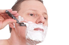 Man with a razor is shaving his cheek Royalty Free Stock Photography