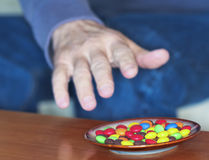 A Man Reaches for Colored Candies in a Dish Royalty Free Stock Images