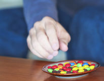A Man Reaches for Colored Candies in a Dish Royalty Free Stock Image