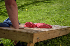 Man reaching into bags game board. Playing cornhole outside in grass on sunny summer day Stock Photos