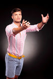 Man reaching with both hands. Portrait of a casual young man reaching with both his hands and looking upward, away from the camera, on black background stock photography