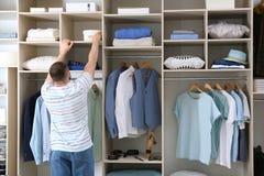 Man reaching for box on wardrobe. Shelf stock photo
