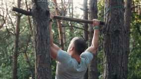 Man reaching for a branch lashed to a tree back view. Man reaching for a branch lashed horizontally between two trees in a forest, close up on his head and arm stock video