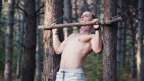 Man reaching for a branch lashed to a tree side view stock footage