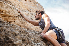 Man reaching for a grip while he rock climbs Royalty Free Stock Images
