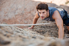 Man reaching for a grip while he rock climbs Royalty Free Stock Photos