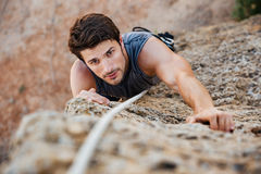 Man reaching for a grip while he rock climbs Stock Images