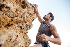 Man reaching for a grip while he rock climbs Stock Photo