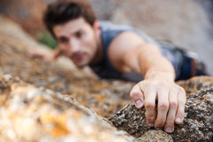 Man reaching for a grip while he rock climbs Stock Image