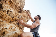 Man reaching for a grip while he rock climbs Stock Photos
