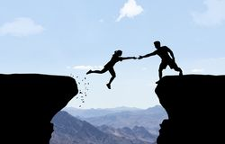 Man reaching hand to woman jumping over abyss. Man gives woman a hand jumping Stock Image