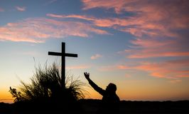 The Salvation Way Cross. Man reaching his hand up to a cross at sunset stock images