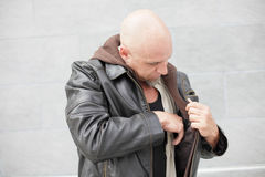 Man reaching into his jacket Stock Photo