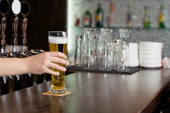 Man reaching for a pint of beer in a pub. Hand of a man reaching for a pint of beer in a pub which is standing on a wooden bar counter royalty free stock photography
