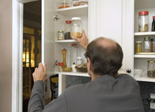 Man reaching for popcorn in empty cabinet Royalty Free Stock Photos