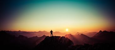 Man reaching summit enjoying freedom and looking towards mountains sunrise. Royalty Free Stock Images