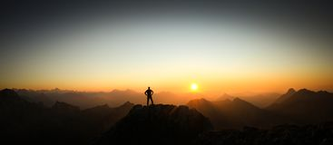 Man reaching summit enjoying freedom and looking towards mountains sunrise. Royalty Free Stock Photography