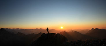 Man reaching summit enjoying freedom and looking towards mountains sunset. Royalty Free Stock Images