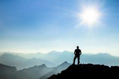 Man reaching summit enjoying freedom and watching towards mountain ranges. Royalty Free Stock Photos