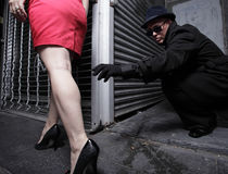 Man reaching to grab the womans leg. Man in an alley reaching out to grab the woman's leg Royalty Free Stock Image