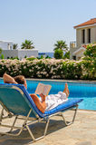 Man read book on deck chair Stock Image