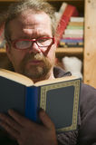 Man read the book front view. Older man sitting in a shadowed corner of a room reading a book Stock Photos
