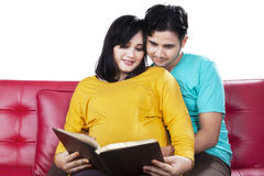 Man read a book with pregnant wife Stock Photo