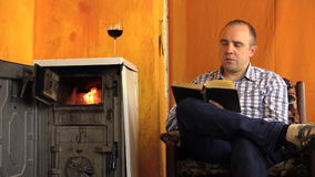Man read book sip wine next to ancient smoldering fire stove Royalty Free Stock Photography