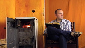 Man read study book near warming stove fire place. Glass of wine stock video footage