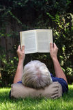 Man reading. Mature man lying on his back on the grass reading a book stock photos